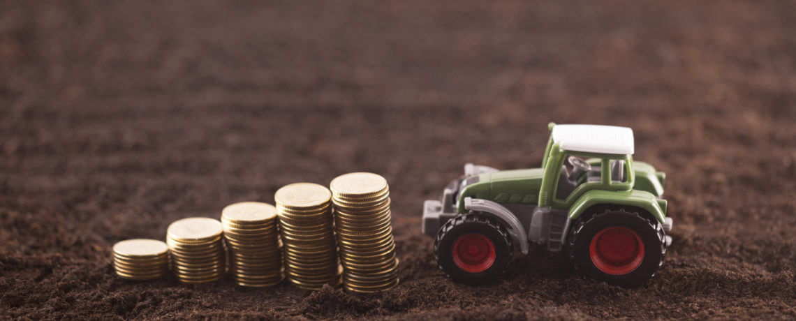 A miniature tractor and an ascending stack of coins rest on a plowed field.