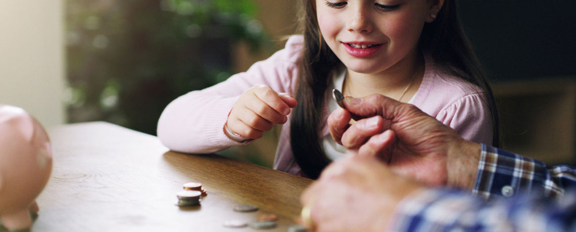 An older man teaches a young girl about financial literacy at a table with coins and a piggy bank
