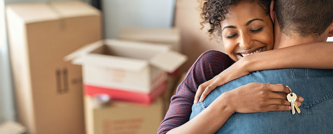 A man hugs a woman as she holds keys to their new home over his back in front of a stack of moving boxes.